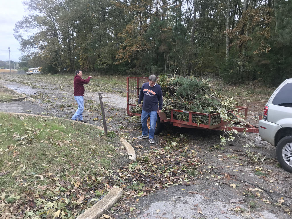 Mr. Elam, Mr. Roberts and Mr. Holt work to clear the parking lot at ACTC of debris after Saturday's storms.